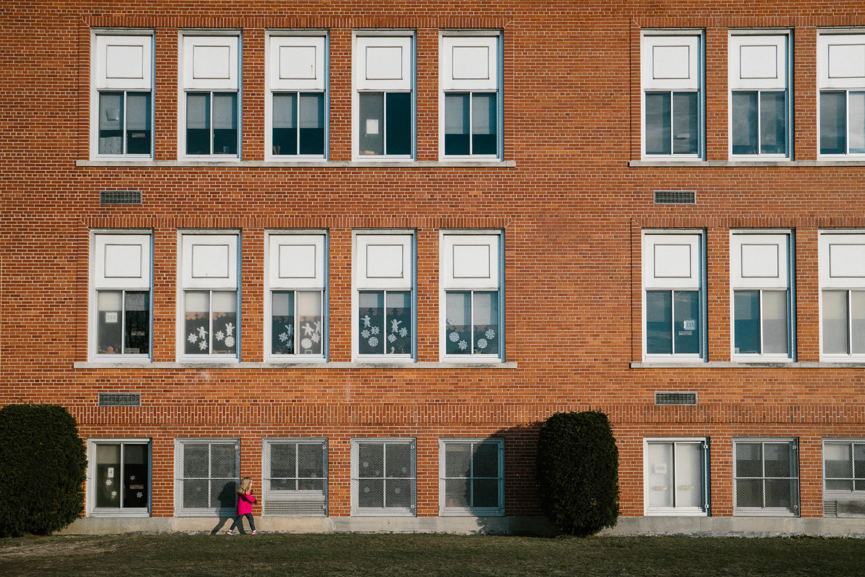 A little girl walks by an elementary school building.