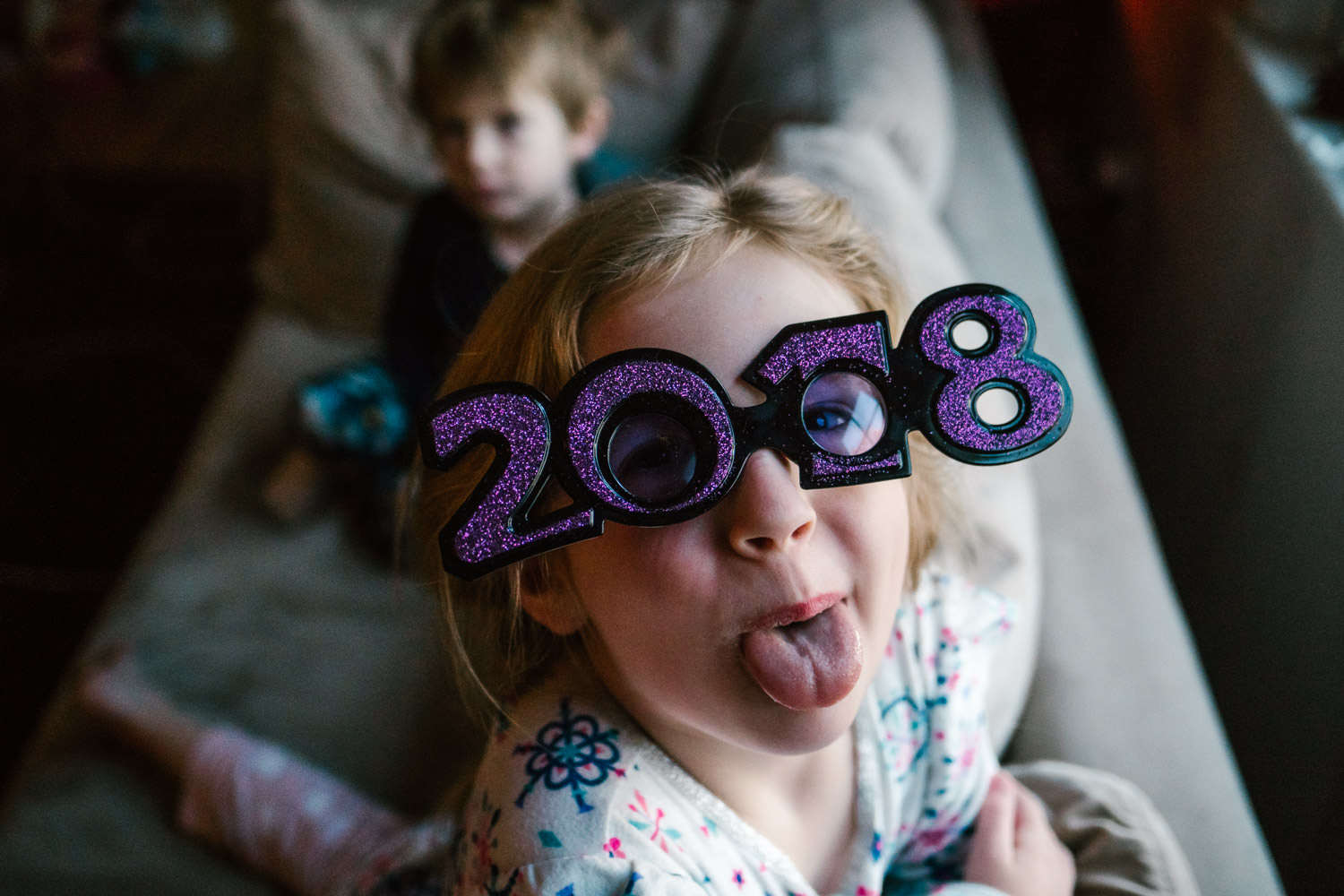 A little girl wearing 2018 glasses sticks her tongue out.