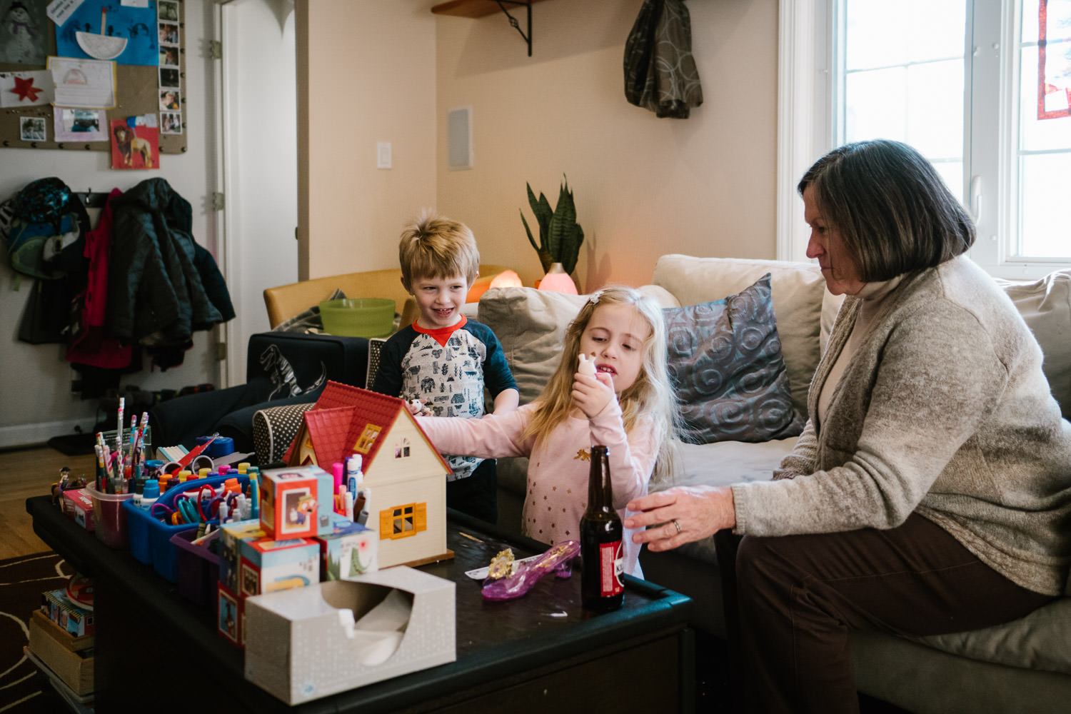Two children talk with their grandmother in the living room.