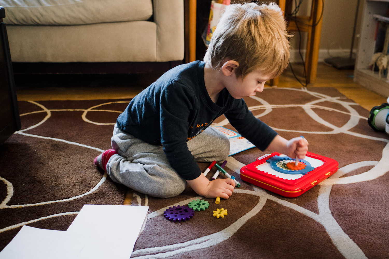 A little boy plays with a spirograph.