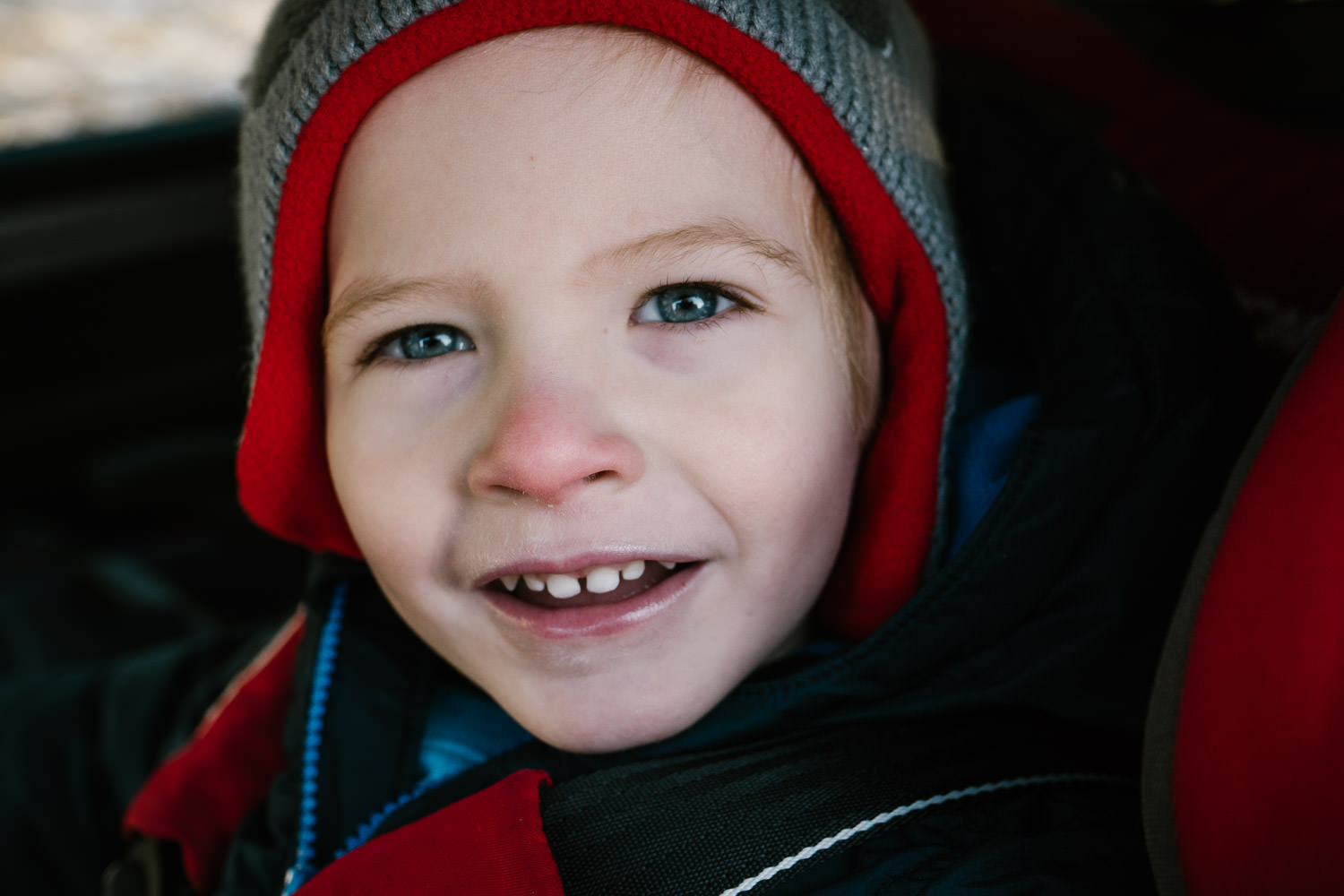 A portrait of a little boy in his car seat.