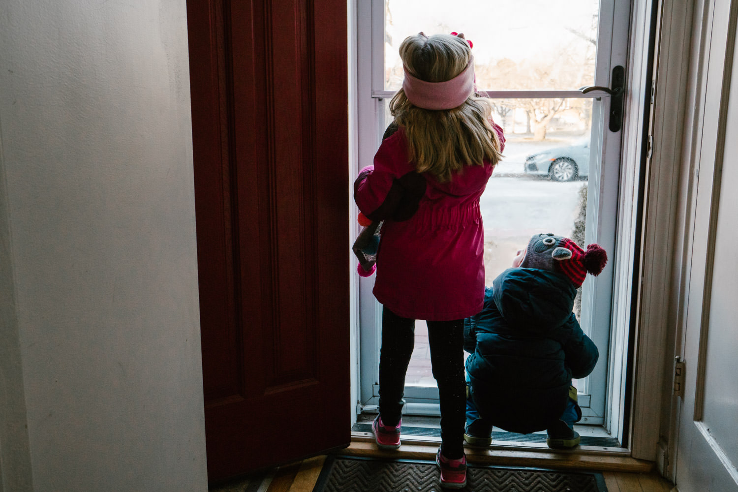 Two children look out their front door on snowy scene.