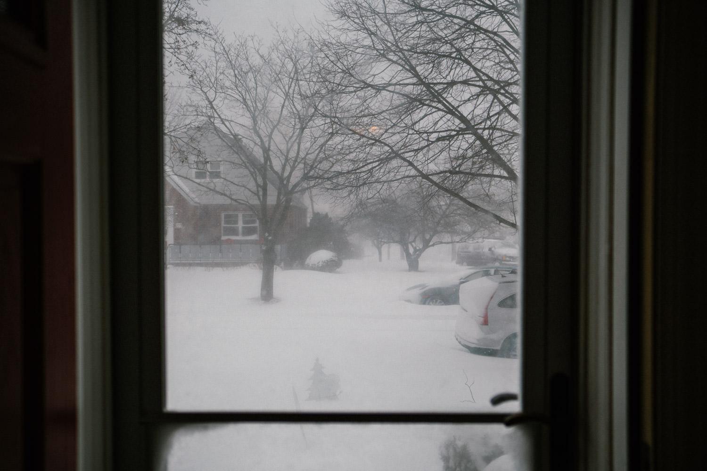 A snowy scene beyond the front door.
