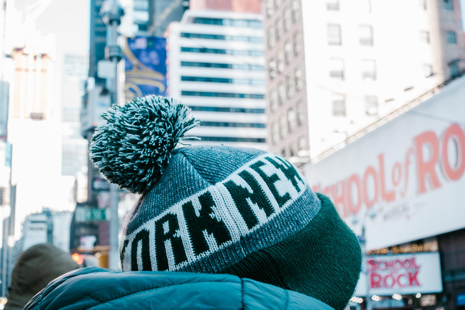 A man wearing a New York City hat on a cold winter day.