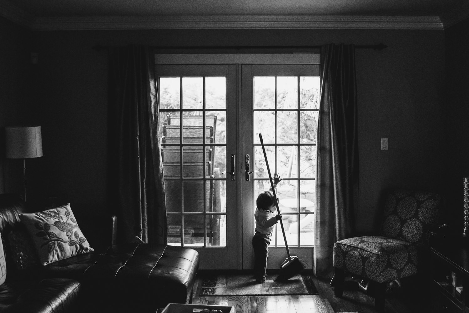 A silhouette of a toddler boy mopping in front of some french doors.