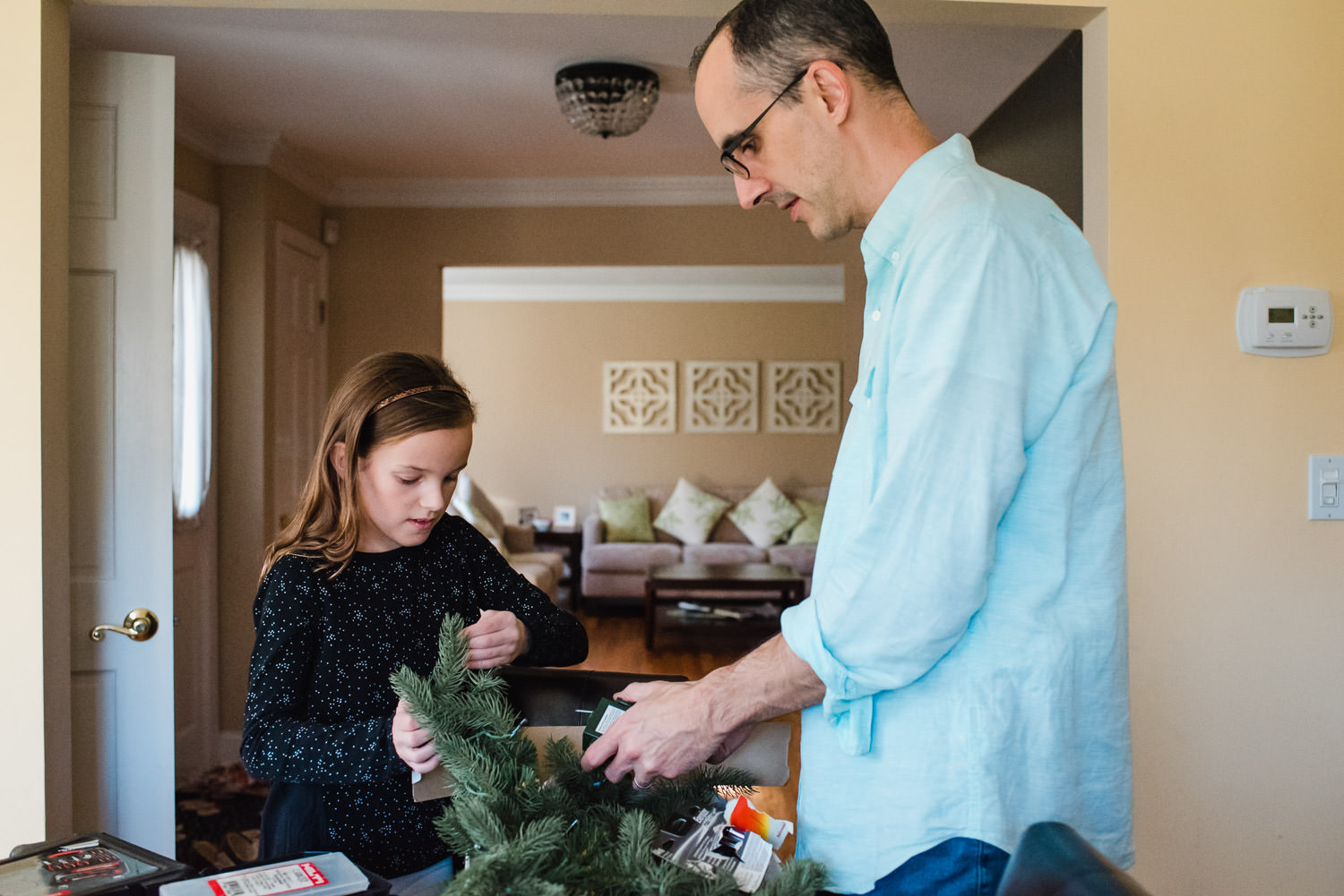 A father and his daughter unpack Christmas decorations.
