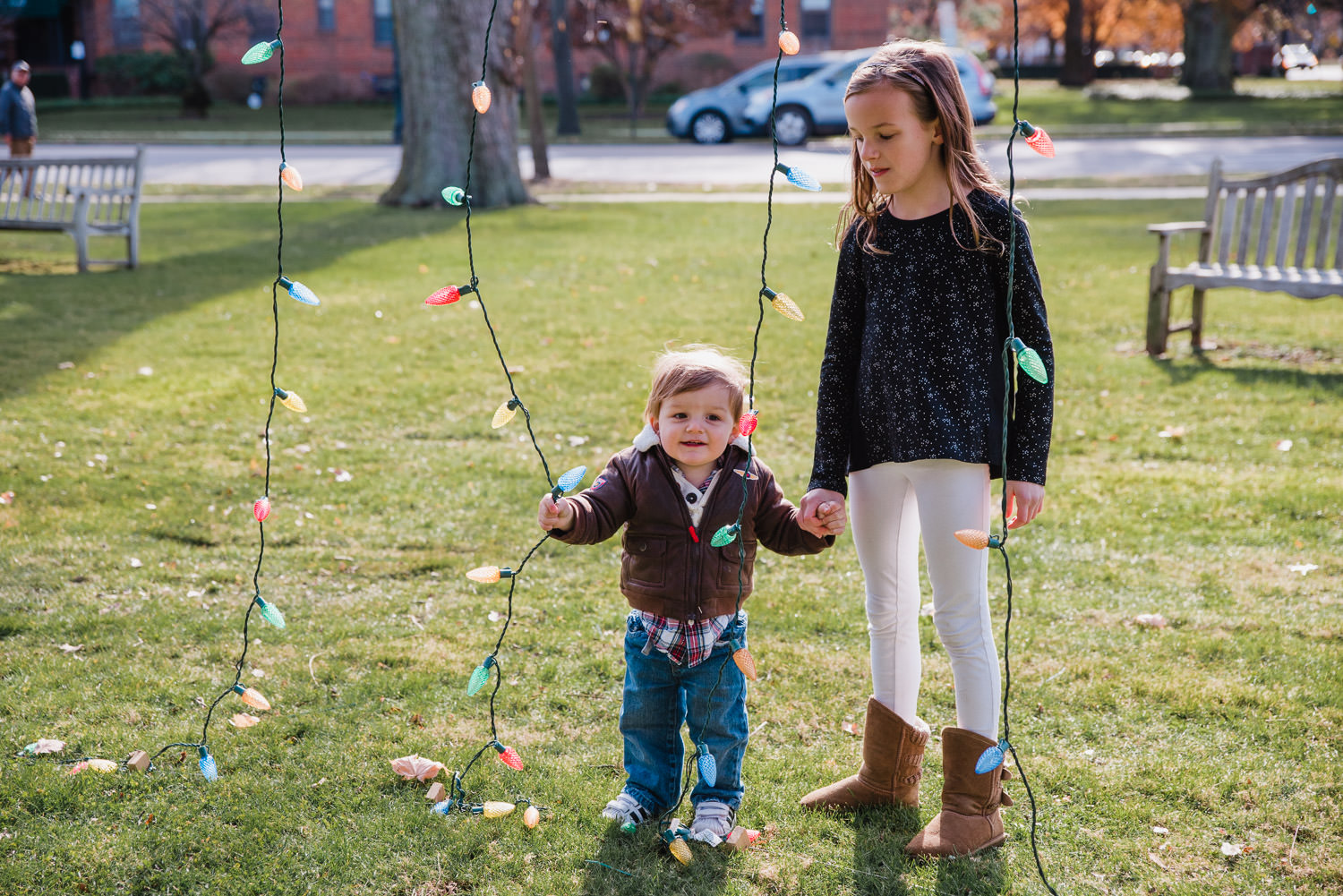 A little girl holds her brother's hand under a tree decorated with lights for the holidays.