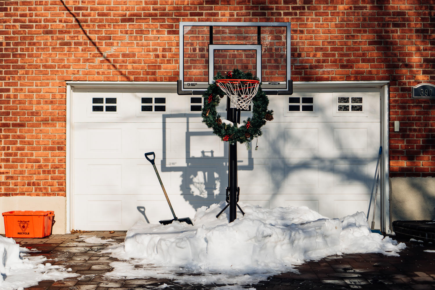 A Christmas wreath hangs on a basketball hoop.