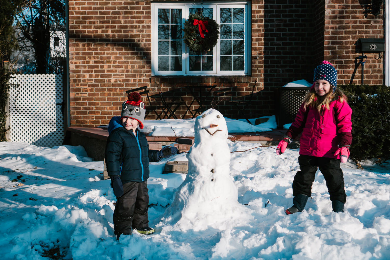 Two children pose next to a snowman they built.