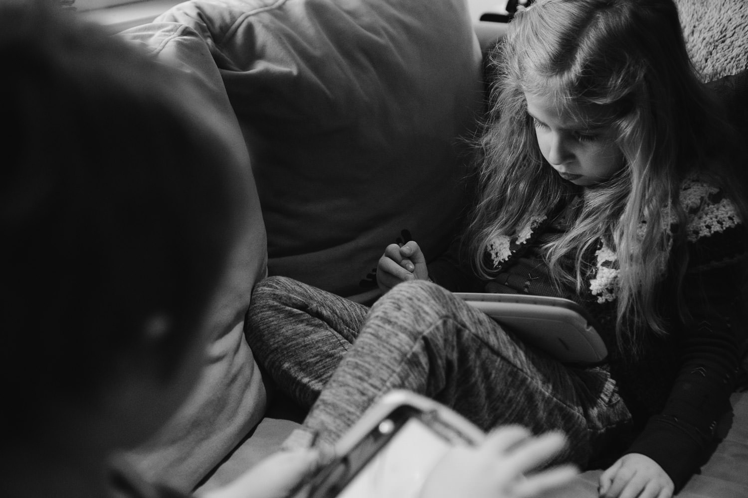 A little girl plays with an iPad on the couch.