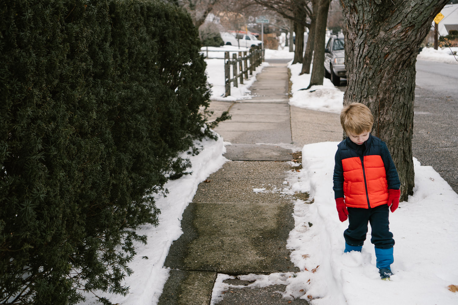 A little boy walks through the snow.