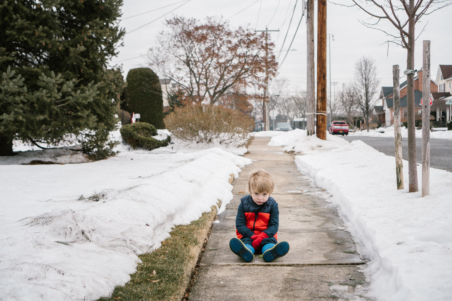 A little boy sits in the middle of a snowy sidewalk.