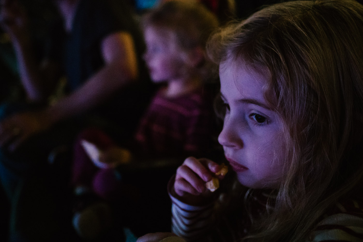 A little girl eats popcorn at Disney on Ice.
