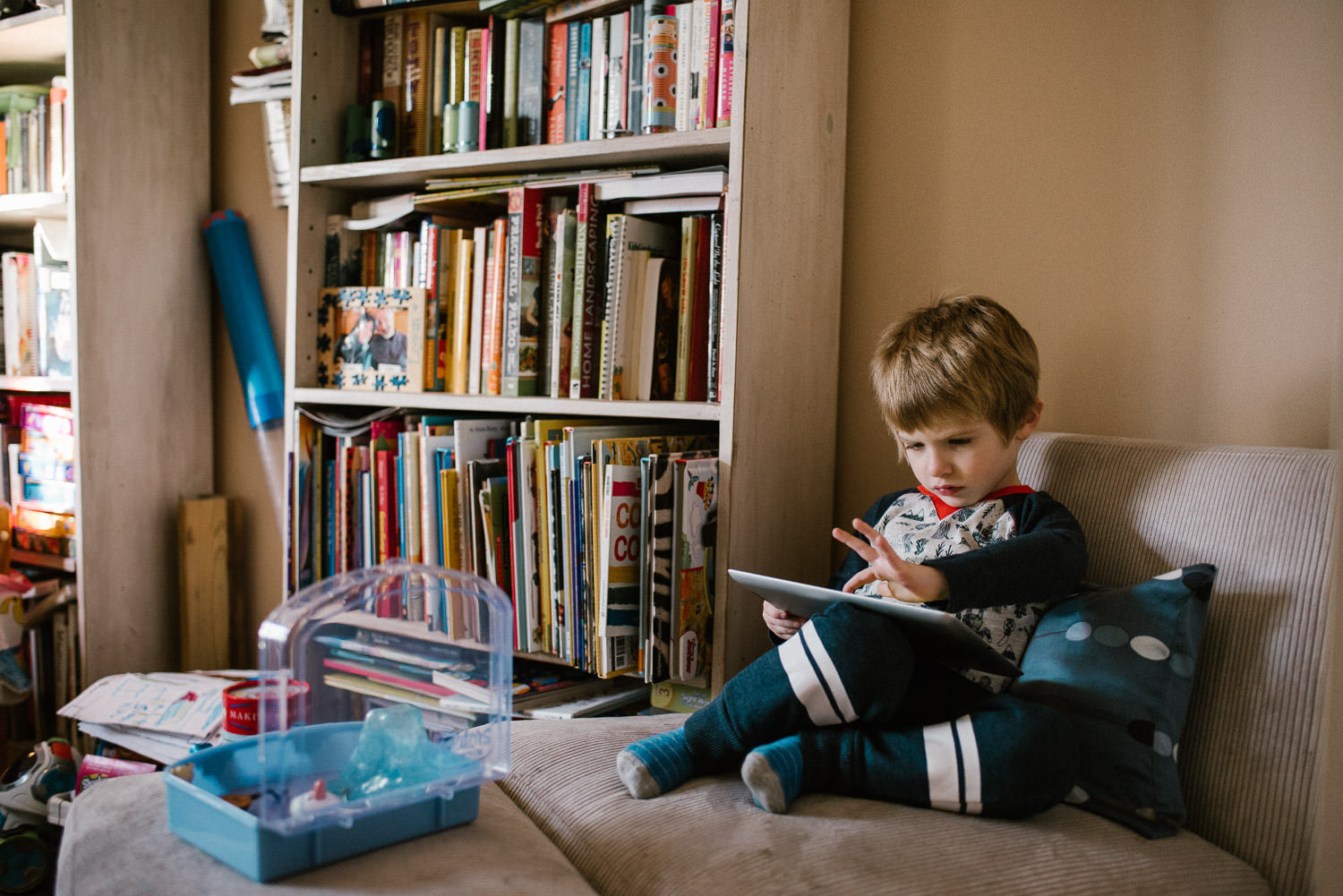 A little boy plays with a tablet in a living room.