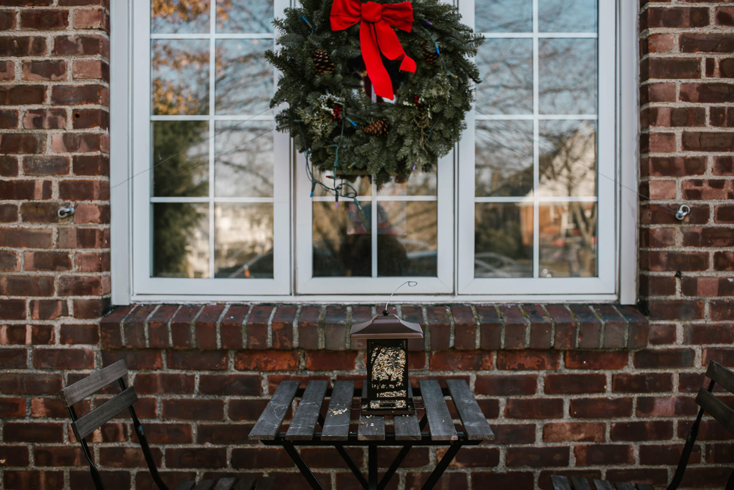 A wreath hangs outside on a window.