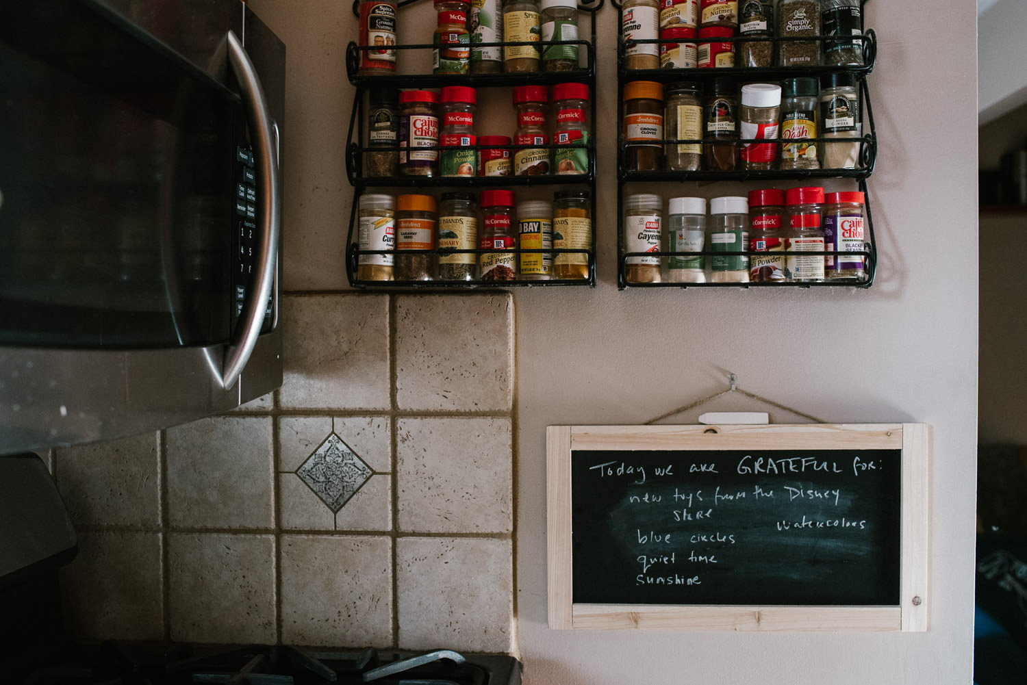 A chalkboard with gratitudes hangs in a kitchen.