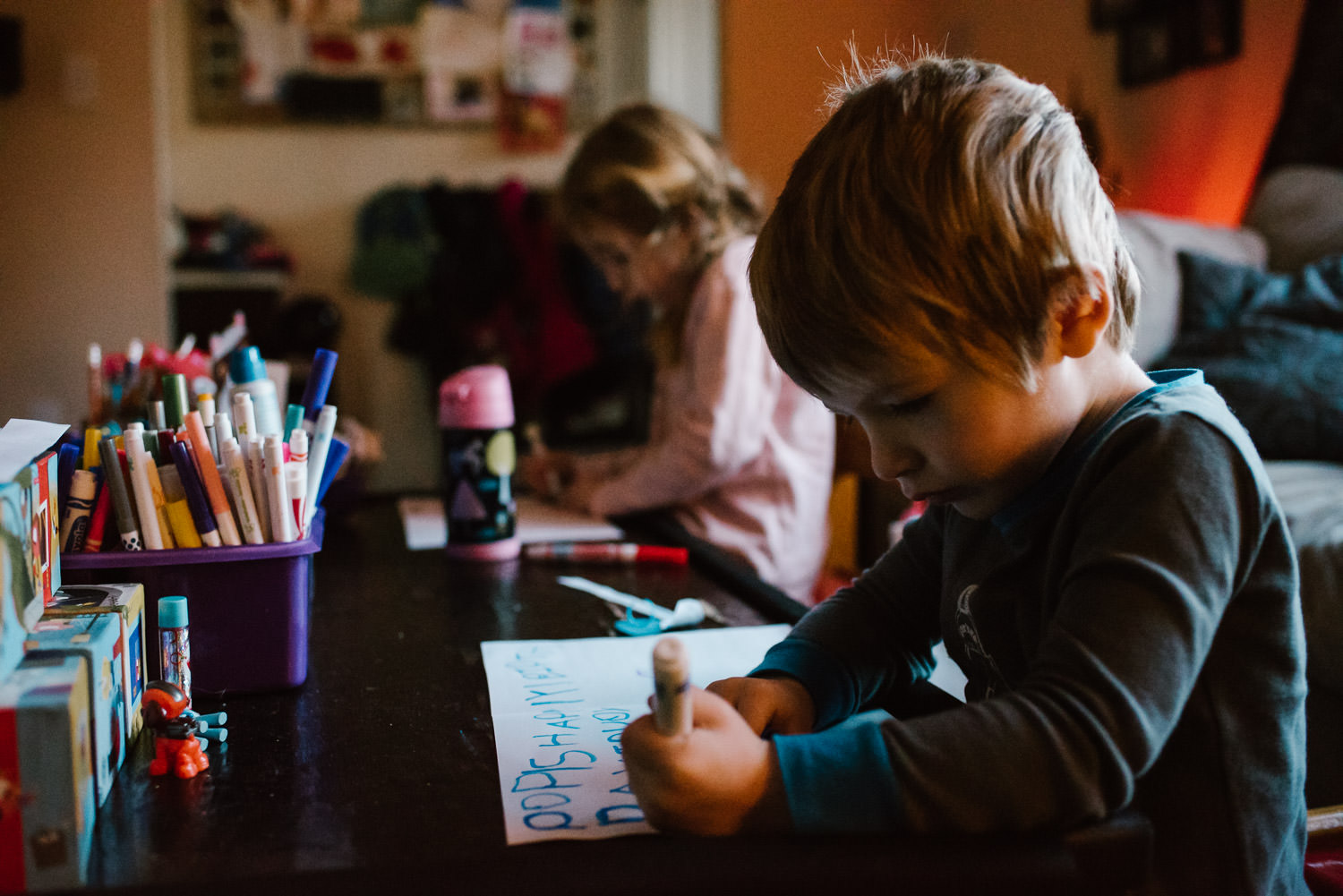 Kids draw in their living room.