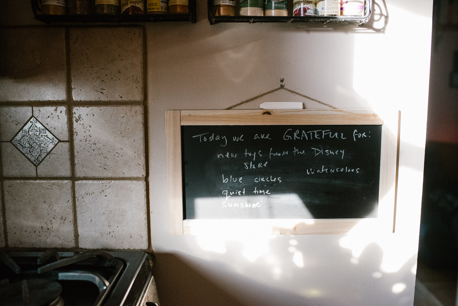 A chalkboard with gratitudes hangs on the kitchen wall.