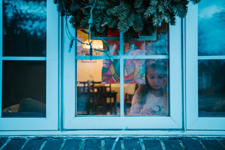 A little girl seen through a window at dusk.