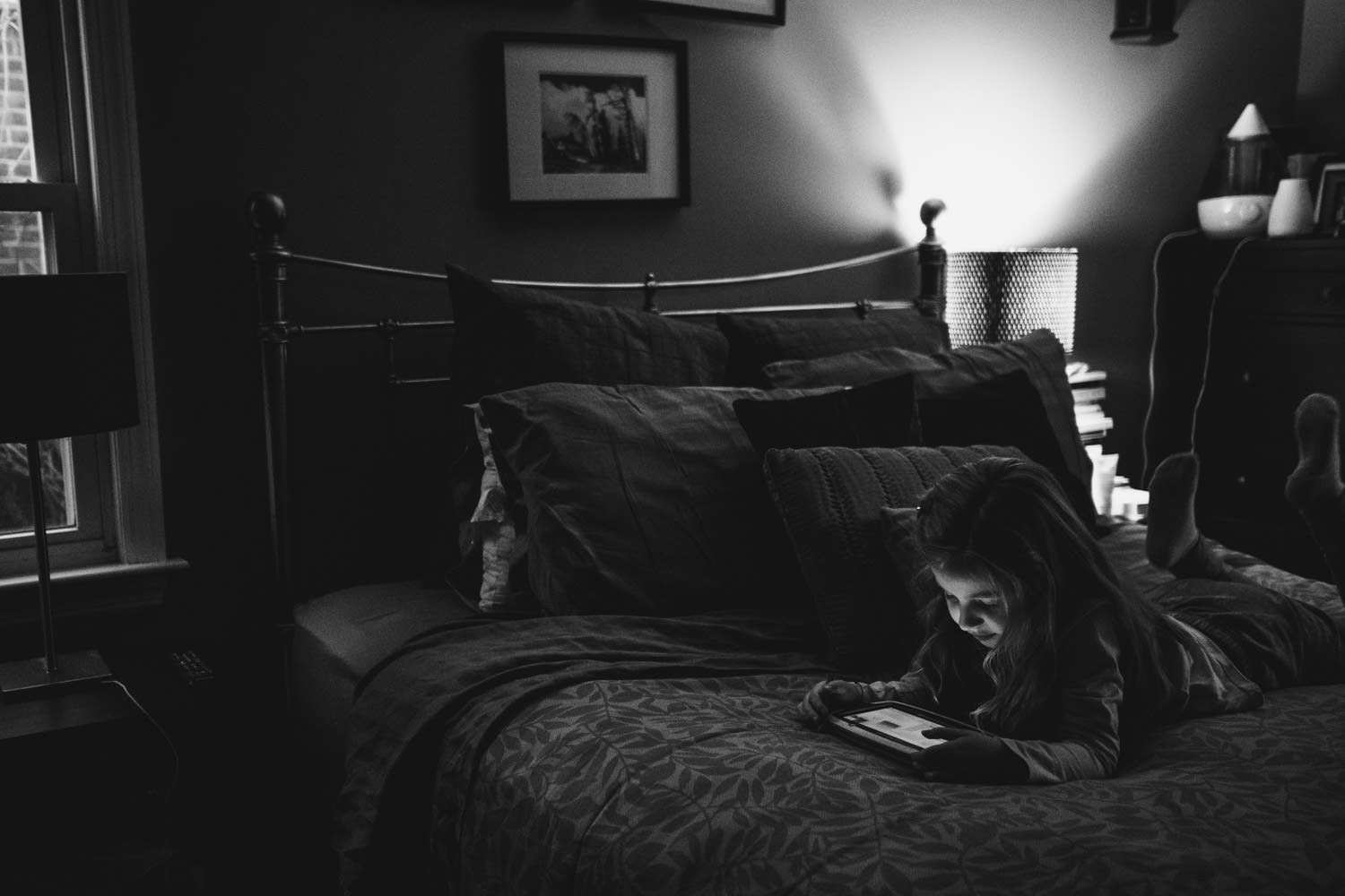A little girl plays with an iPad on her parents' bed.