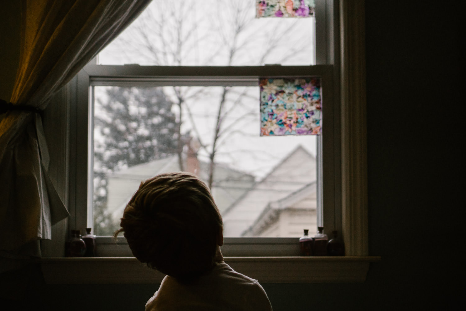 A little boy looks out his bedroom window.