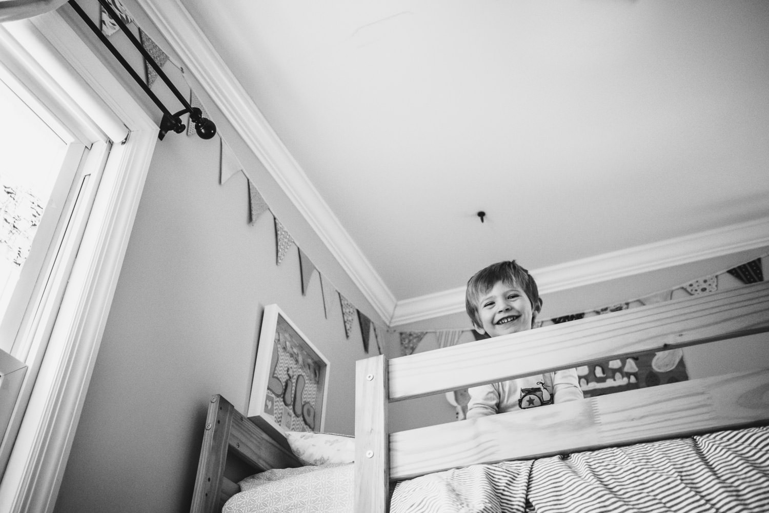 A little boy peers down from the top bunk of his bed.