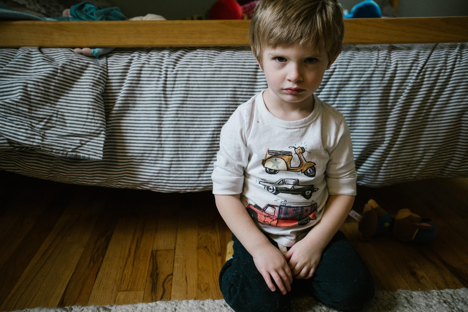 A little boy sits grumpily in his bedroom.
