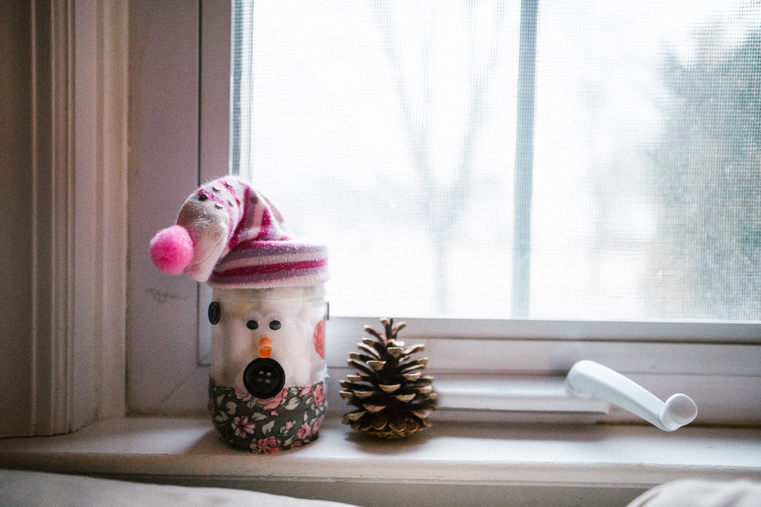 Winter crafts perched on a window sill.