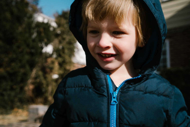 A portrait of a little boy in a parka outside.