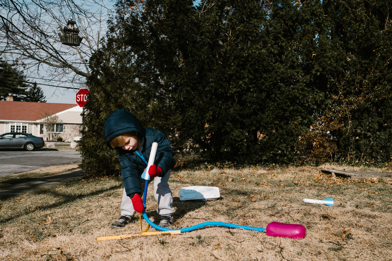 A little boy plays with a stomp rocket in his front yard.