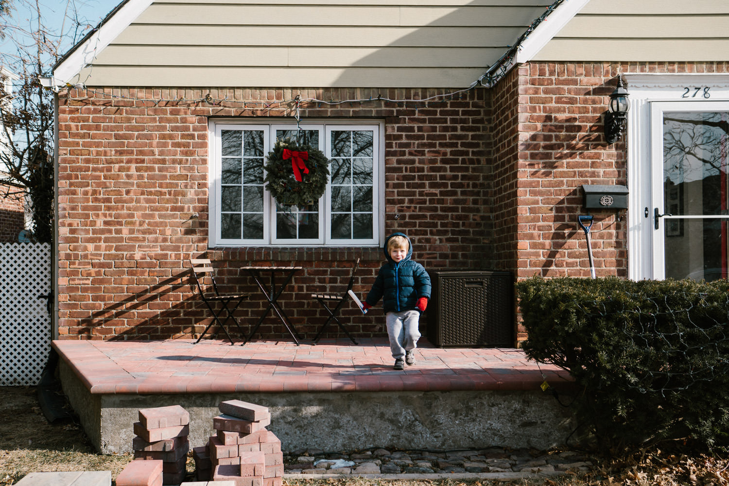 A little boy stands on his porch holding a stomp rocket.