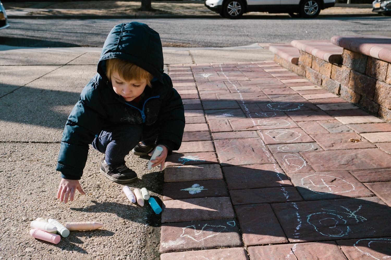 A little boy plays with sidewalk chalk.