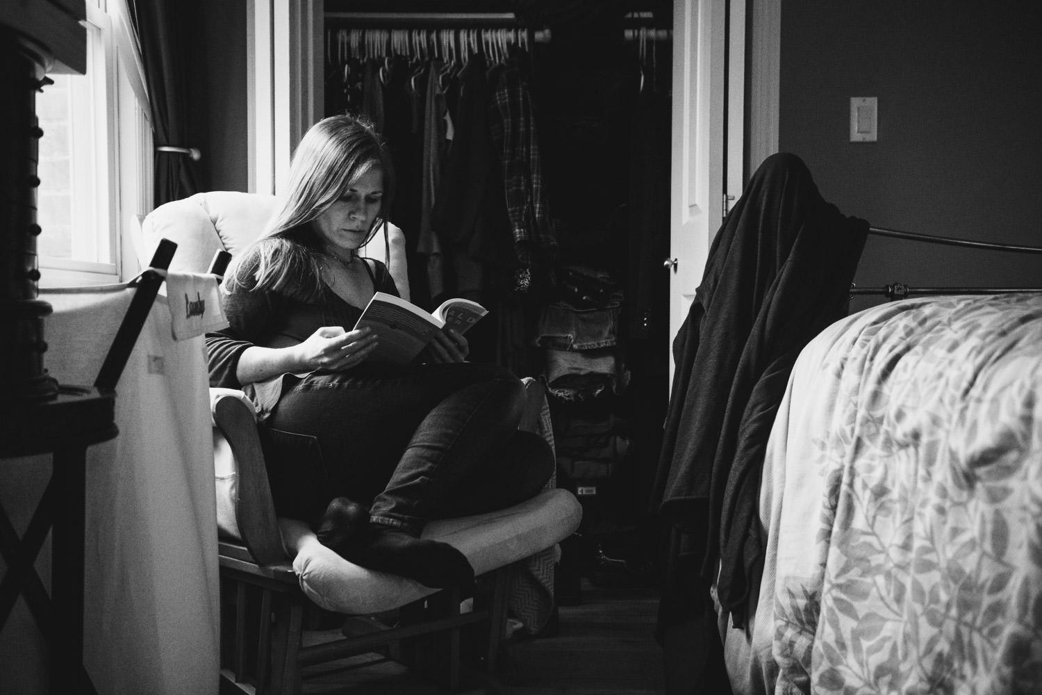 A woman reads a book in a rocking chair in her bedroom.