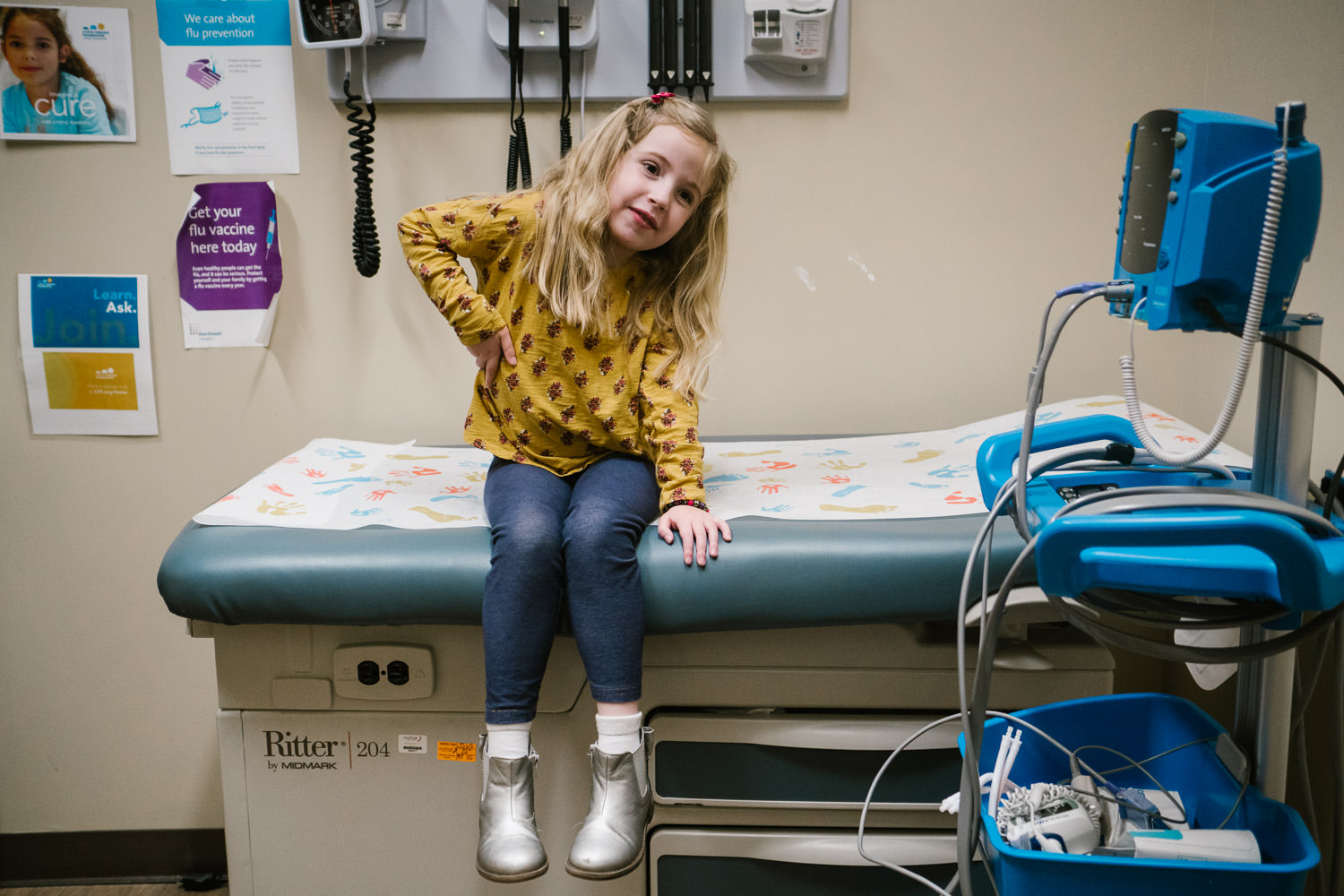A little girl sits on an examining table in a doctor's office.
