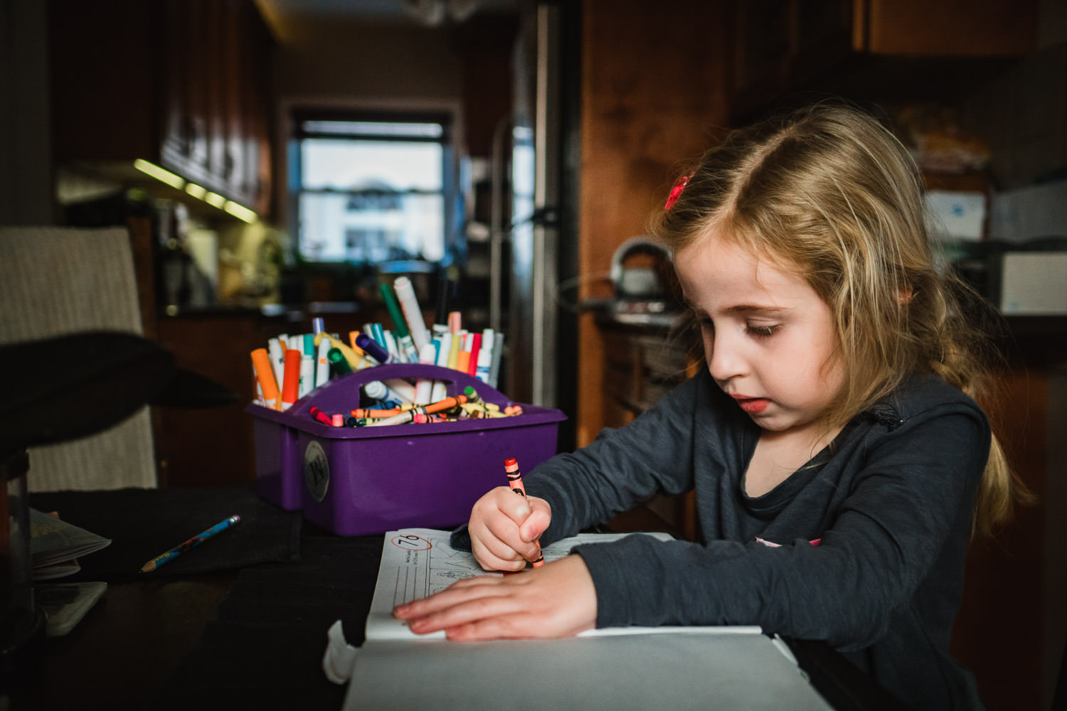 A little girl sits and does homework at her kitchen table.