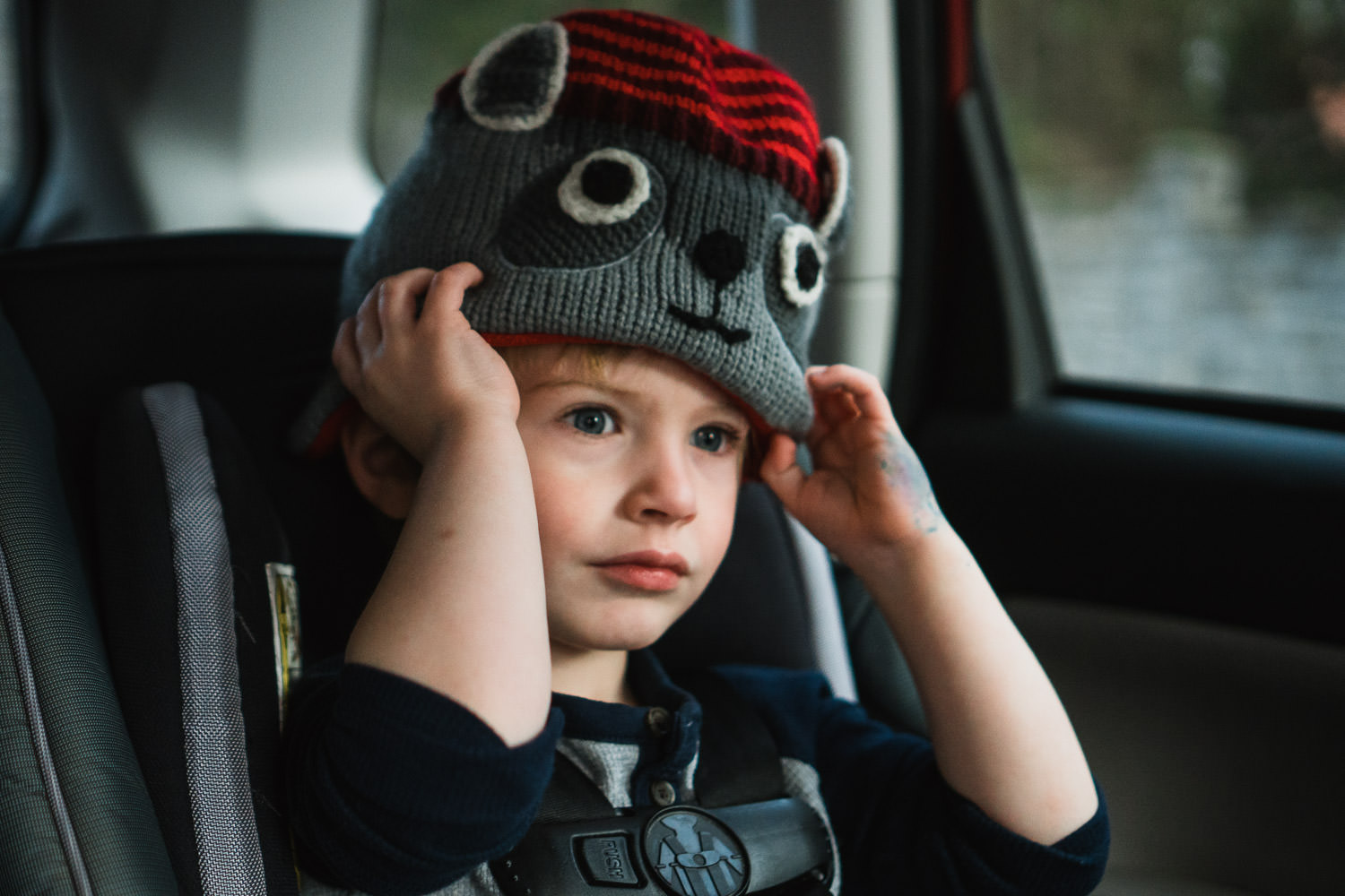 A little boy pulls on a hat in his carseat.