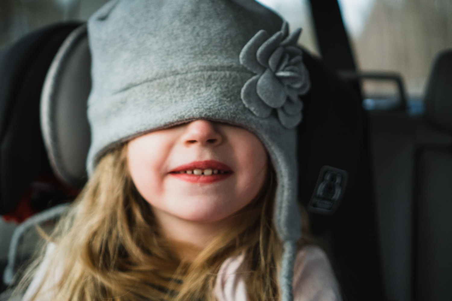 A little girl smiles with her hat pulled over her eyes.
