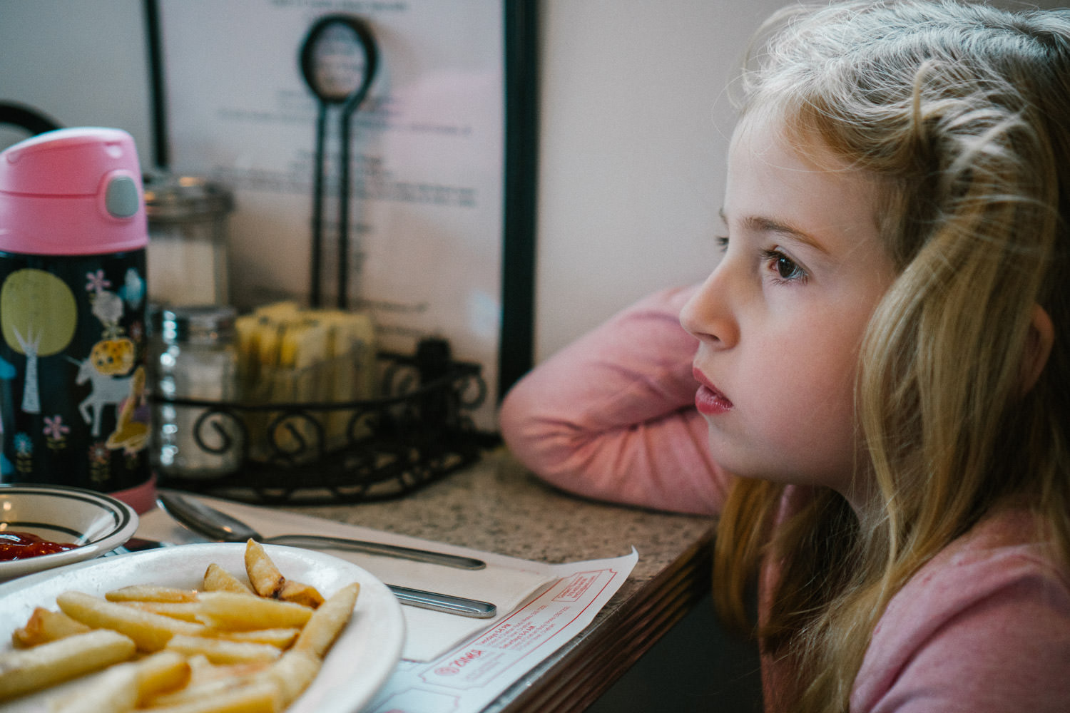 A little girl zones out at a table in a diner.