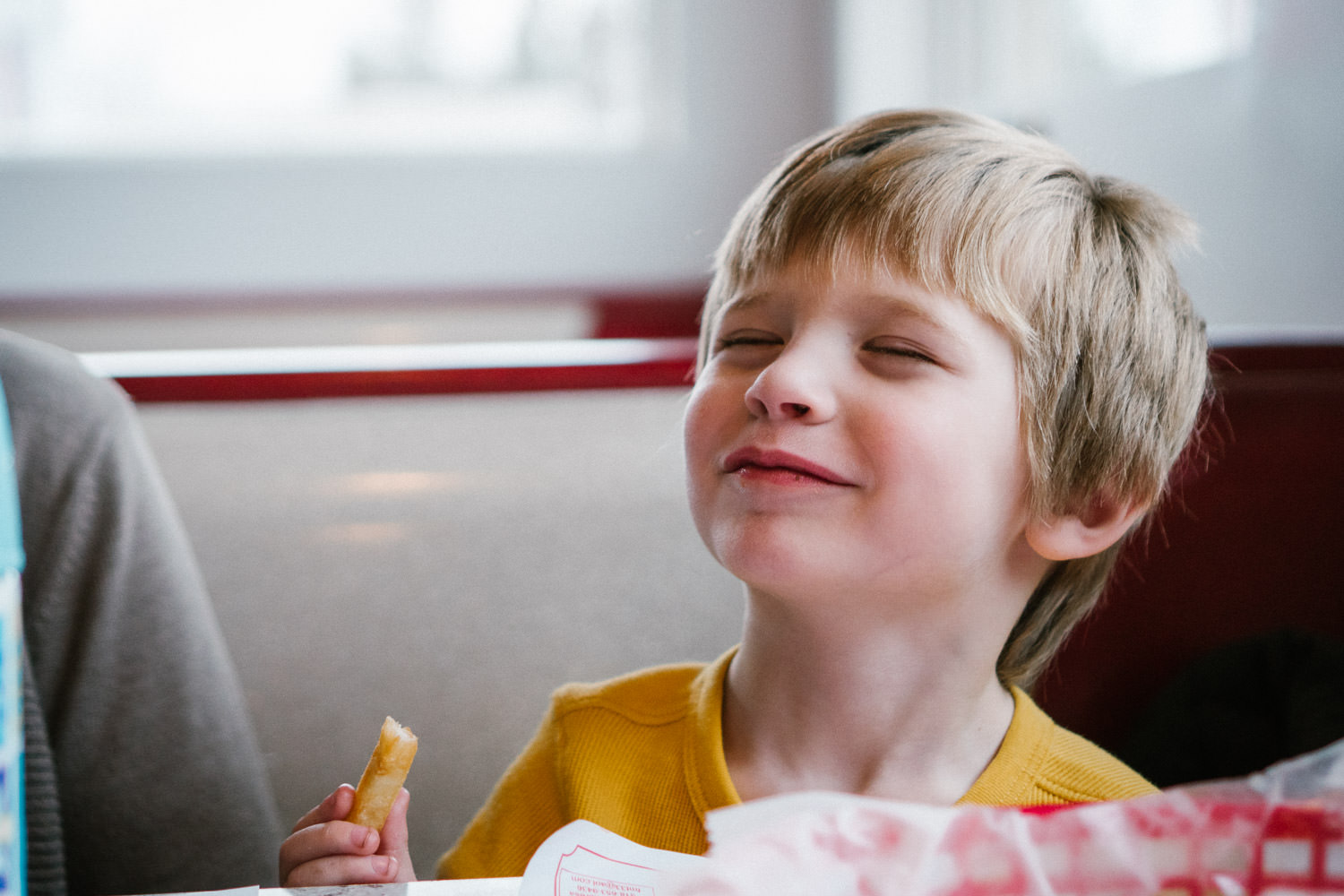 A little boy smiles while eating a french fry in a diner.