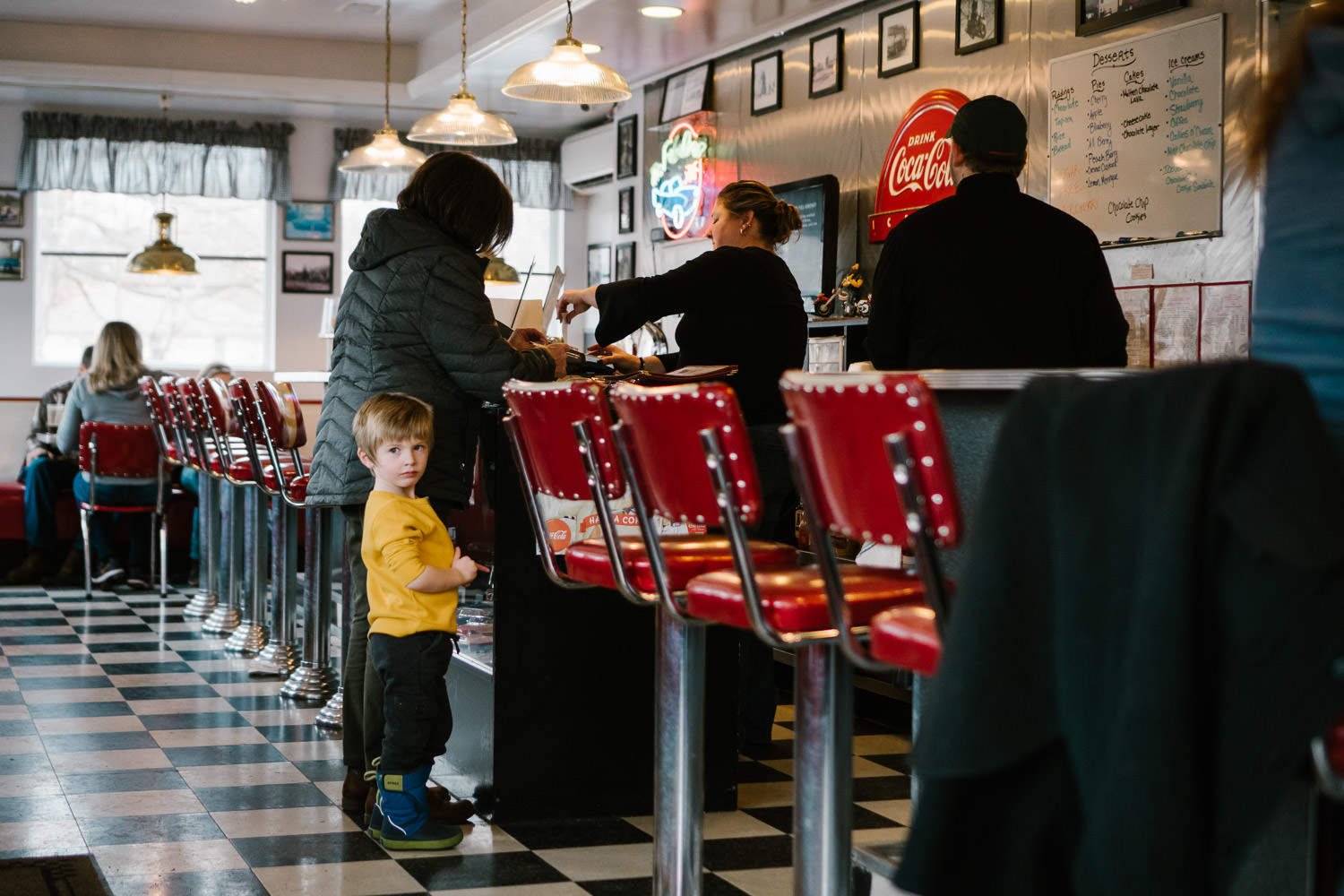 A little boy and his grandmother stand at the register in a diner.