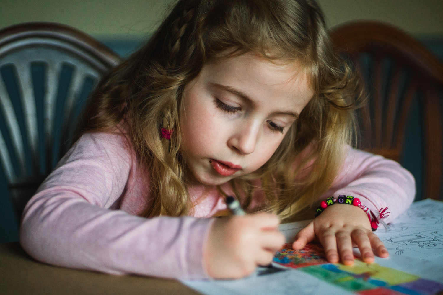 A little girl colors diligently with a crayon.