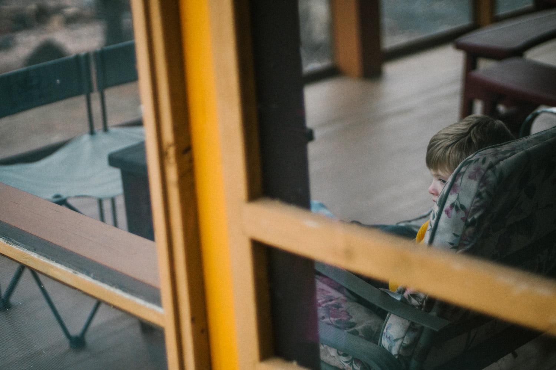 A little boy sits by himself on a porch.