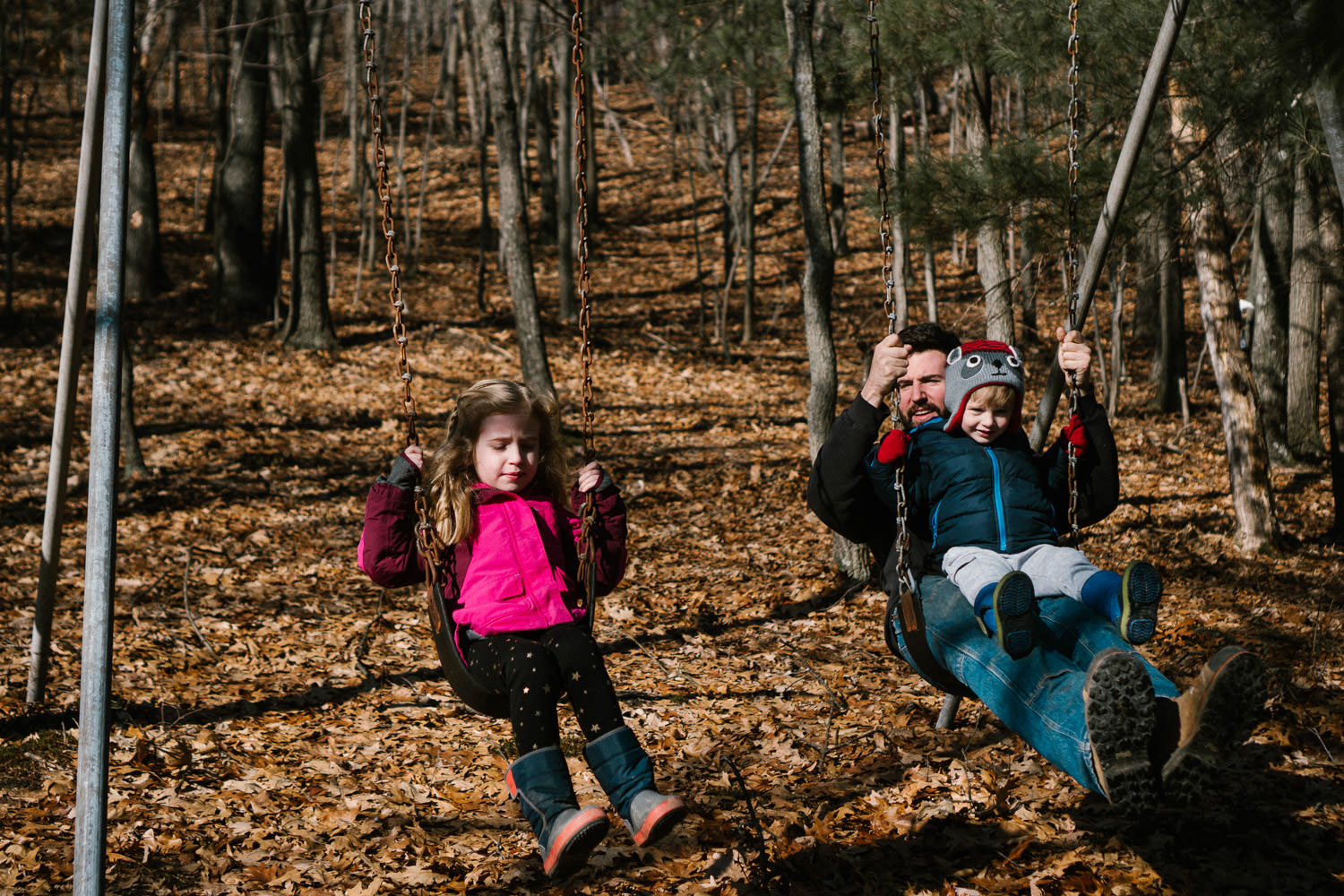A family swings on a swingset in the woods.