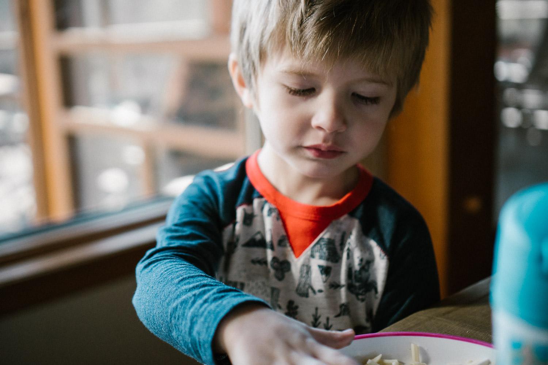 A little boy eats lunch.