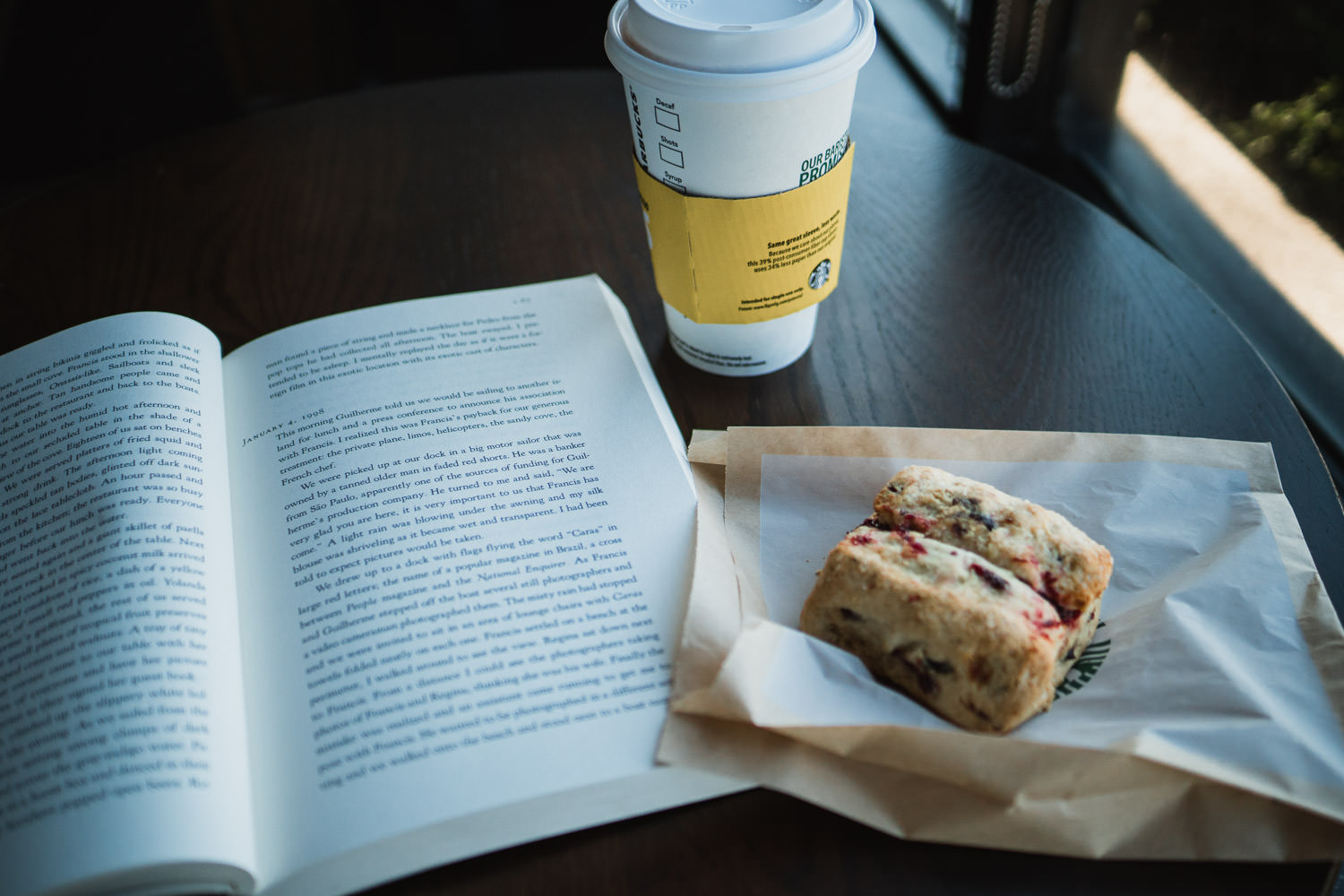 A book and a coffee and a scone.