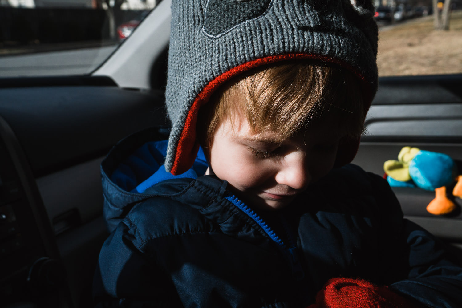 A little boy sits in the front seat of a parked car.