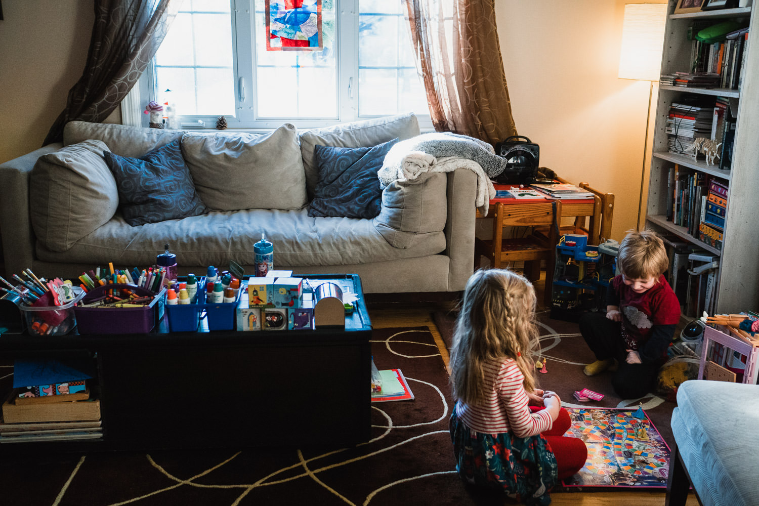 Two children play board games in their living room.