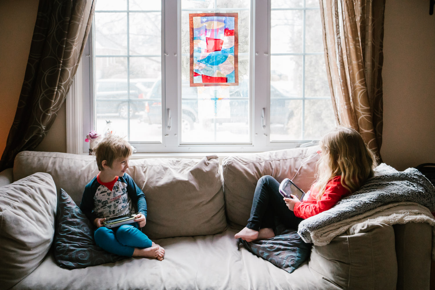Two children sit on their couch in front of their living room window.
