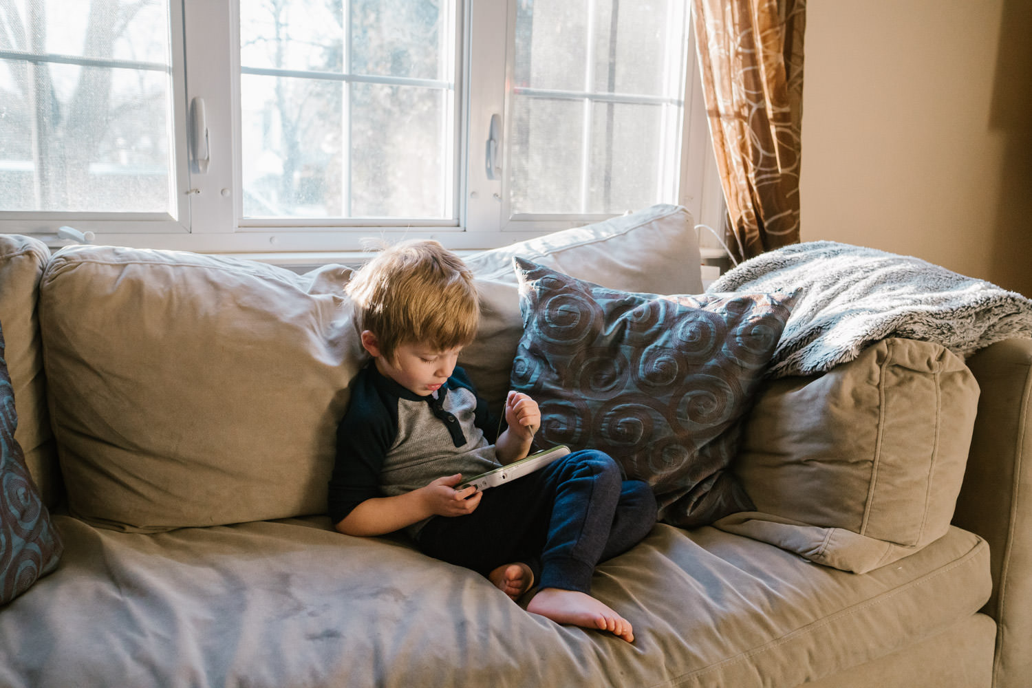 A little boy plays with a tablet on a couch.