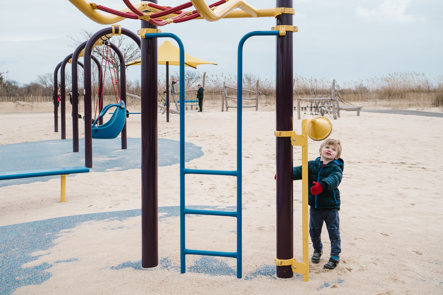 A little boy plays at a playground at Captree State Park.